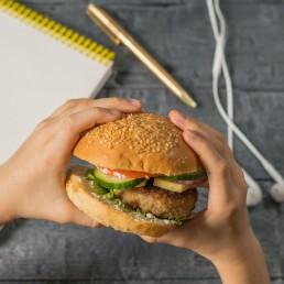 Mani di teenager con hamburger